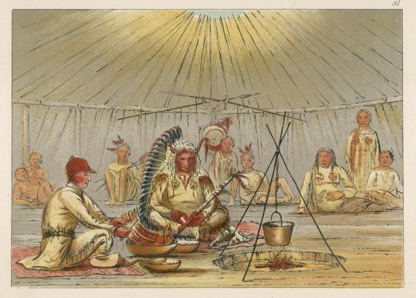 George Catlin sits cross- legged around a fire, in a Native American tent, with Mah-to-toh-pah, the second chief of the Mandans