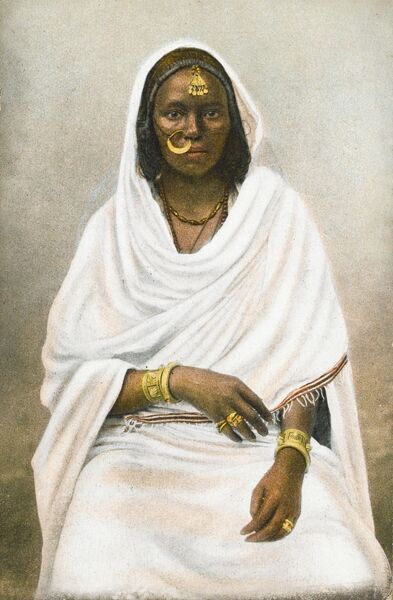 An indigenous African Egyptian woman, with golden jewellery (including a large hooped nose ring), large bangles and enveloped in a long white toga-style shawl wrap