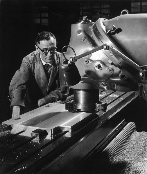 A factory worker uses a piece of precision shaping machinery to cut and level a thick metal block. Photograph by Heinz Zinram