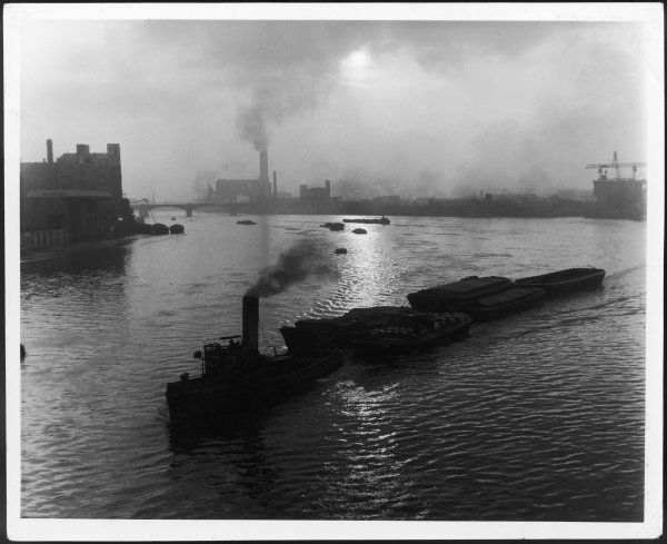 A tug hauls industrial barges along the River Thames, photographed from Chelsea Bridge at flood tide