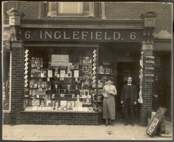 The proprietors stand outside their newsagent's shop, which is also a stationer and tobacconist, located in a Hampshire seaside town
