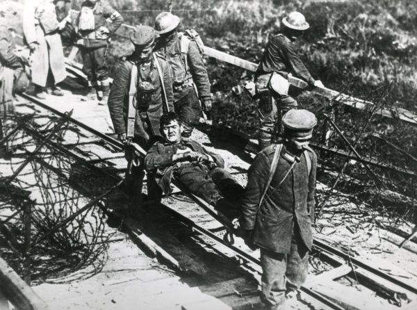 An injured American soldier is carried on a stretcher during action at Boureville, Forest of Argonne, north eastern France during the First World War. Date: 26 September 1918