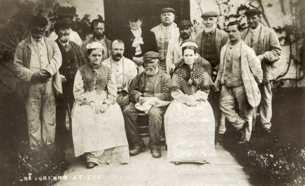 Uniformed inmates of the Bosmere and Claydon Workhouse, Barham, Norfolk. The smartly dressed woman, centre rear, is probably a local organiser for the Brabazon scheme where workhouse inmates made craft items which were then sold. Date: circa 1907