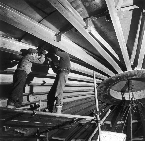 Two welders, standing on a scaffold, use spanners to tighten the nuts securing sections of the centrepoint of a large domed roof for an aluminium liquid methane tank at Canvey Island. Photograph by Heinz Zinram
