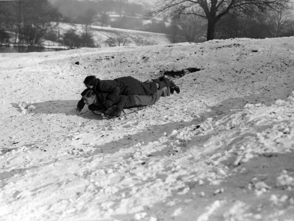 A young couple get close as they share an intimate sledge ride in the snow at Hampstead Heath, north London! Date: 1930s