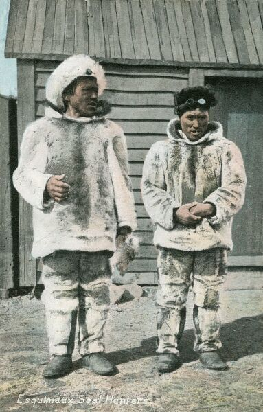 Two inuit seal hunters in full fur and hide clothing. The hunter on the right has goggles to protect his eyes against the glare from the pure white snow