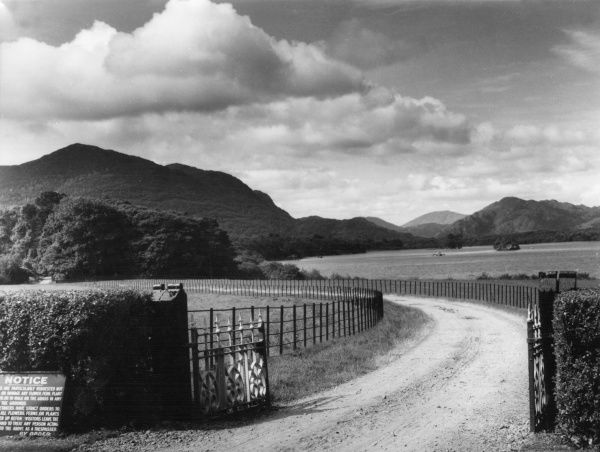 The entrance gates to Bourne Vincent Memorial Park and Muckross Abbey, showing Castlelough Bay on Loch Leane, near Killarney, County Kerry, Ireland. Date: 1960s