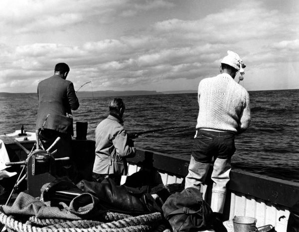 Fishermen sea angling off the coast of County Antrim, Northern Ireland. Date: 1960s