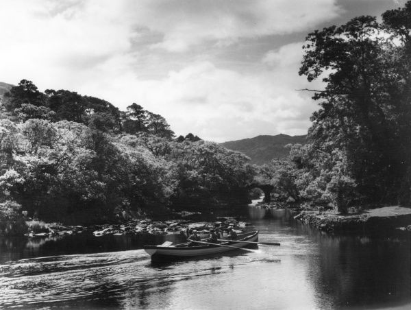 A boat on its way to collect tourists who have descended from the Gap of Dunloe, at the meeting of the Waters and Old Weir Bridge, Muckross Estate, Killarney, County Kerry, Eire. Date: 1950s