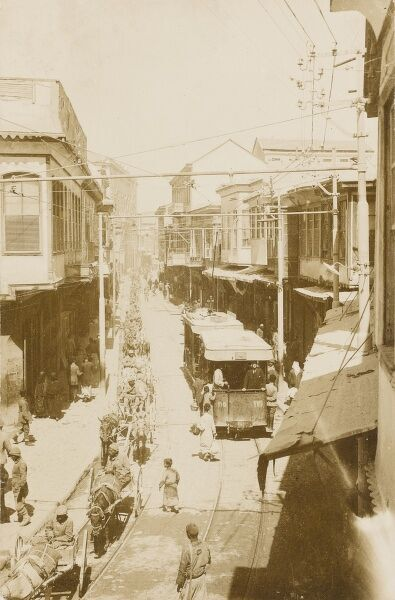 A street scene with a tram number 115. The women are wearing Syrian-influenced clothing. The roofs are slightly aligned for snow. Interesting long mule train on left of road. Iskenderun - Turkey. Also known as Alexandretta in Greek and in English Alexandrette