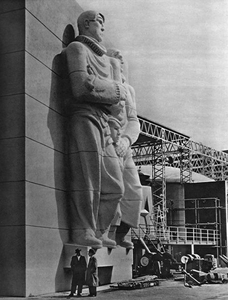 View of a colossal sculpture by the Austrian sculptor, Siegfried Charoux, entitled The Islanders, on the facade of the Sea and Ships Pavilion at the Festival of Britain exhibition on the South Bank, London. The three figures represent a man