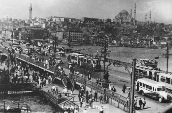 A view across the Galata Bridge and Golden Horn, with motorbuses, trams, cars and pedestrians packing the crossing
