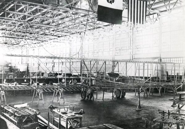 An Italian aircraft workshop, probably during the First World War, with the flags of Italy and the USA visible above. Date: circa 1915-1918