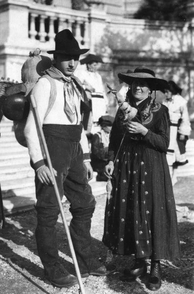 A man and woman, possibly mother and son, dressed in traditional costumes at Piedmont, Italy. Note the knife in his cummerbund and pom-poms on her boots. Date: 1930s