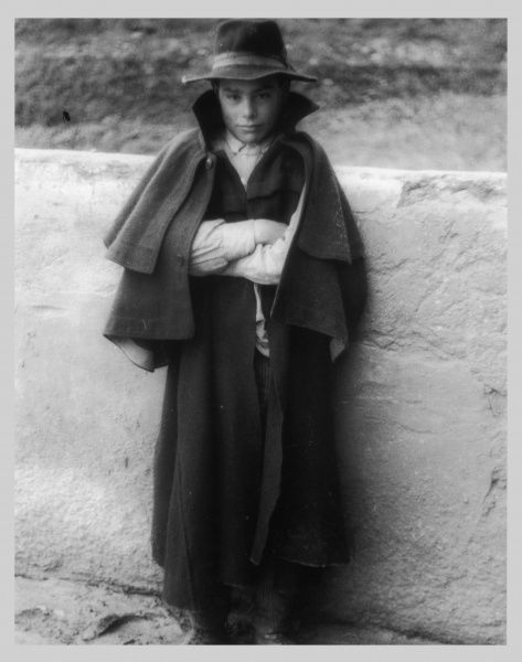 An Italian boy, smartly dressed in a hat and long cloak, an immigrant to Britain, living in the Saffron Hill, area of London, EC1
