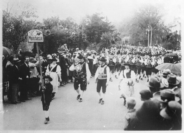 Men and women and children from Maia Bassa (Italy), taking part in a procession, dressed in Tyrolean costume