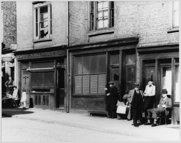A group of Italian men sit in the sun or lounge in doorways in a Saffron Hill street separated from the women and children outside a shop belonging to F Ciccone