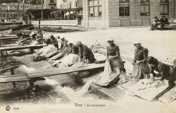 Italy - Riva del Garda in the northern Italian province of Trentino. Washerwomen cleaning clothes and bed linen on the banks of Lake Garda. Date: 1907