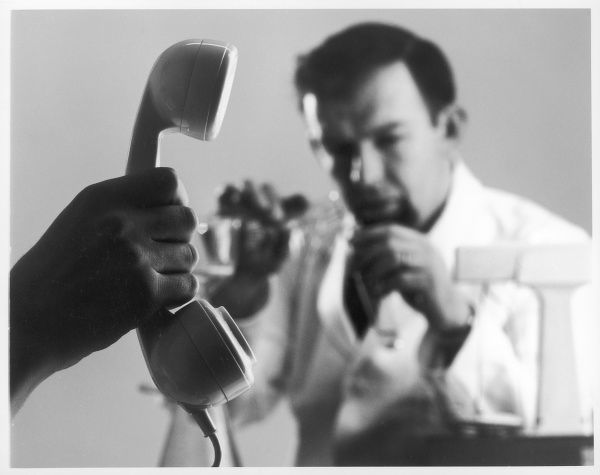 A telephone is held up in front of a scientist