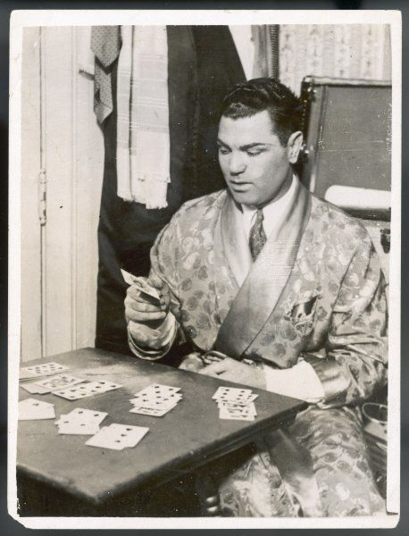"JACK DEMPSEY, world heavyweight champion between 1919 and 1926, was once described as ""187 pounds of unbridled violence""; here he asks the cards to tell him his future"