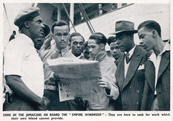 Jamaican men on board the Empire Windrush who have come to Britain to seek work; some of the men, dressed smartly in jackets and ties, are reading a newspaper