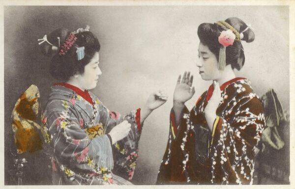Japan - Geisha girls at play. They may be either mock fighting (the geisha on the left appears to have balled fists) or possibly playing scissors-paper-rock, which originated in Japan. Date: circa 1910s