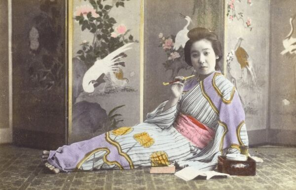 Japan - Reclining Geisha girl in a fine kimono smoking before a beautiful decorative screen. Date: circa 1910s