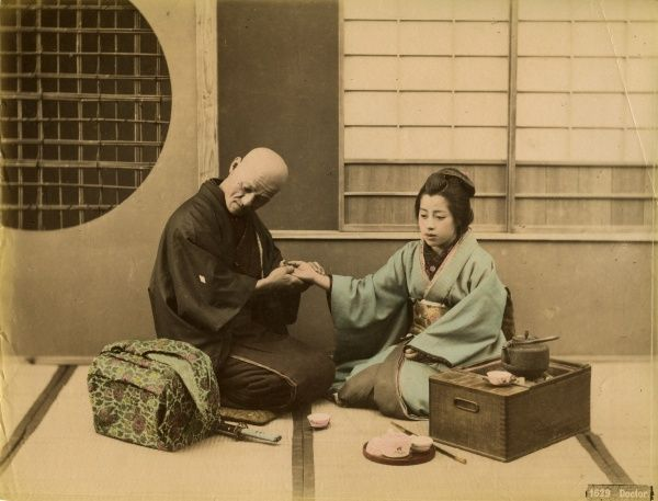 A Japanese doctor with his medical bag examines or massages the hand of a female patient