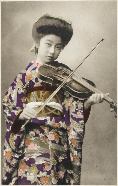 A stunning photographic postcard depicting a young Japanese girl playing the voilin