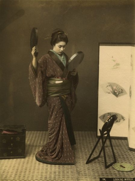 A Japanese lady, keen to make sure she is immaculately dressed, uses mirrors to check her hairstyle and appearance