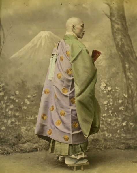 A Japanese man (possibly a spiritual man?) in a studio wearing traditional costume and wooden geta footwear