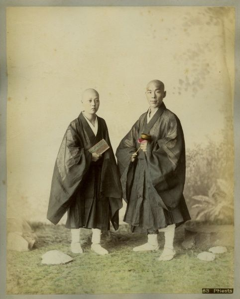 Two Japanese monks in traditional costume, with shaved heads and long cloaks
