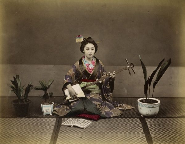 Japanese lady in traditional dress with a stringed musical instrument