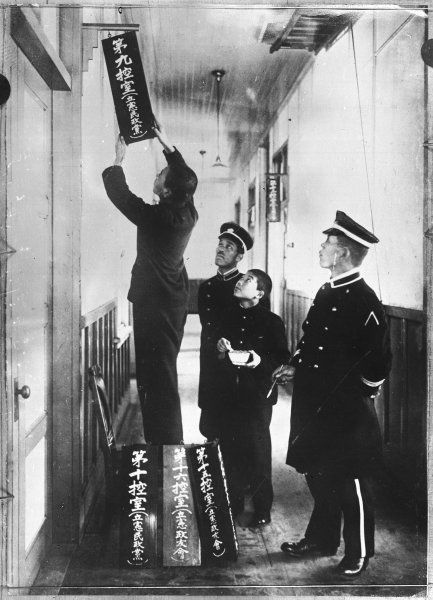 Officials putting up name signs in the Japanese Houses of Parliament, Tokyo, Japan
