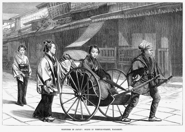 A lady of Nagasaki is drawn along Temple street, while a servant walks beside her carrying her shoes