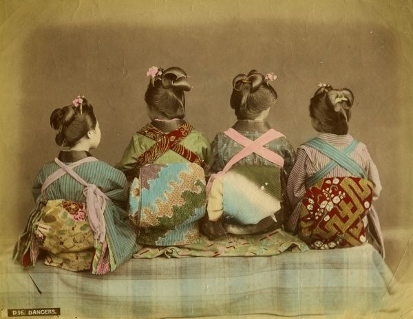 Four Japanese dancers wearing traditional kimonos sit with their backs to the camera