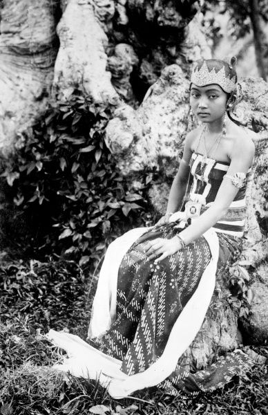 A native dancing girl in a traditional elaborate costume and headdress, Java, Indonesia. Date: 1930s