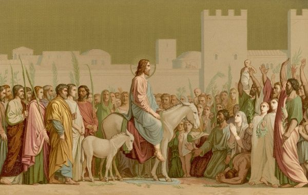 He rides into Jerusalem on a donkey, as prophesied : his followers carry palm leaves, hence the day will be commemorated as Palm Sunday
