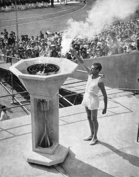 The athlete and Surbiton medical student John Mark, a former Cambridge blue and quarter-miler, lights the bowl on the peristyle, on the east terrace of Wembley Stadium. The audience then sang the Olympic Hymn. Date: 1948