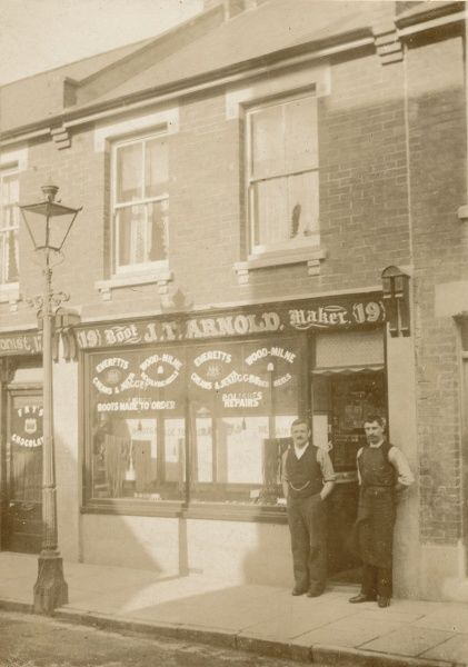 Mr J T Arnold, bootmaker, stands outside his shop with his assistant : he sells laces and polish, repairs boots and shoes and makes boots to order. Location unknown
