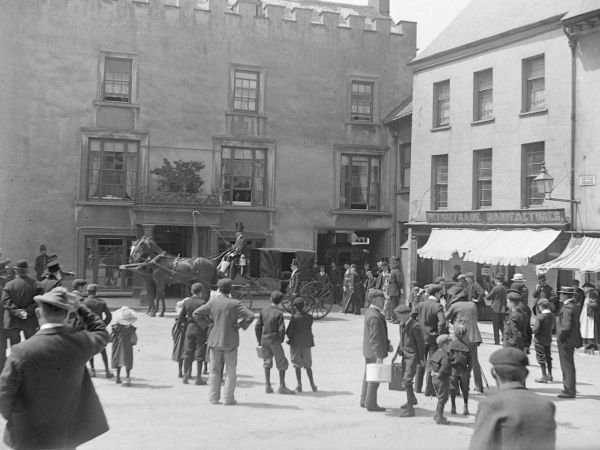 A judge's horse-drawn carriage outside the Castle Hotel in Castle Square, Haverfordwest, Pembrokeshire, Dyfed, South Wales. The townspeople stop in their tracks to see what will happen next