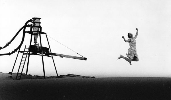 A middle aged woman in a flowery dress jumping for joy, near a gravel pit. What has made her so happy is anyone's guess!
