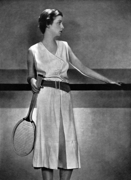 An exclusive Bystander photograph showing the designer, Elsa Schiparelli's practical but stylish jupe-pantalon tennis dress in light white woollen weave with a waist belt of orange coloured tussore