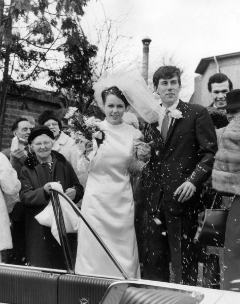 A couple of newlyweds are showered with confetti! Date: 1960s