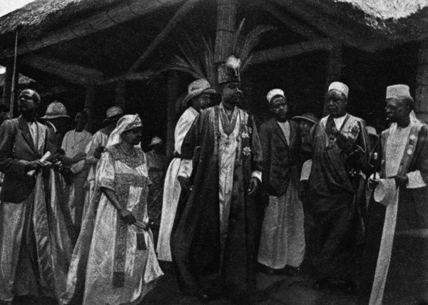 King Daubi Chwa, the Kabaka of Buganda with his consort, Queen Irene and his ministers at Mengo.During the Duke and Duchess of York's visit to Uganda, King Daubi Chwa was invested by the Duke with the K.C.M.G.. Date: 1925