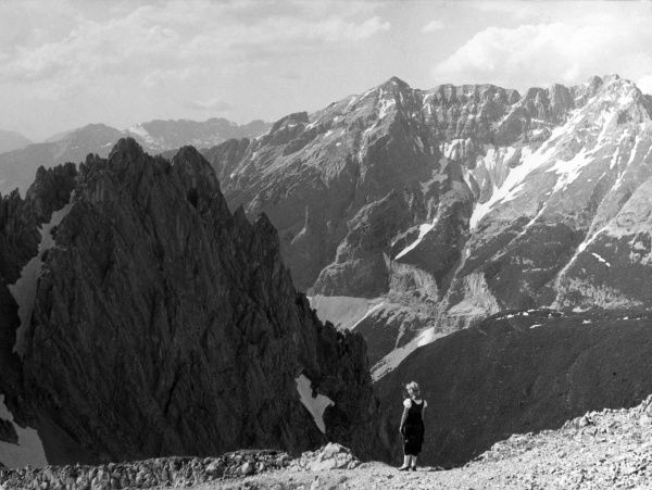 A girl admires the breathtaking scenery of the Karwendel Pass, Austria. Date: 1930s