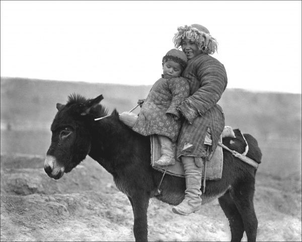 Two siblings ride on a small pony, wrapped up against the cold. Both are from the Xinjiang province of China - close to Kashgar. Photograph by Ralph Ponsonby Watts
