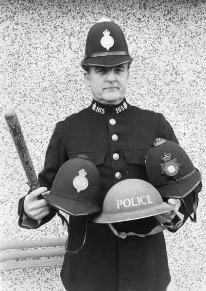 Ken Searle, police historian, wearing the tunic and winter helmet of 1910-1936. He is holding a summer issue helmet (1910-1936, left), a Second World War tin helmet (centre) and a helmet issued at the time of Queen Elizabeth II's coronation