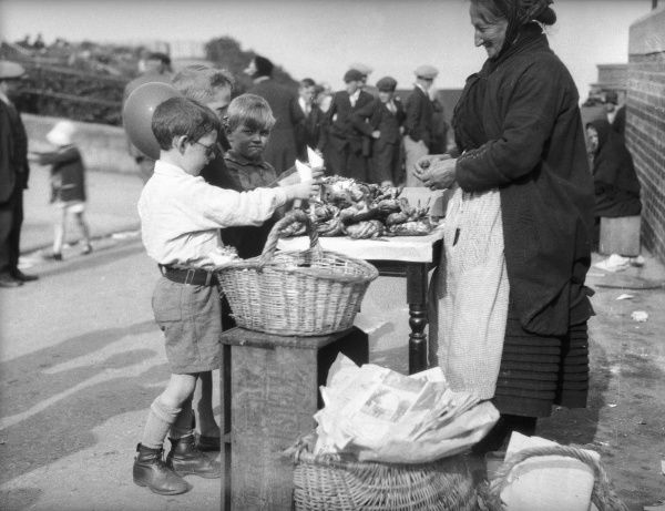 Two little boys buying crabs from an old lady on a stall in Cullercoats, North Shields, north east coast of England