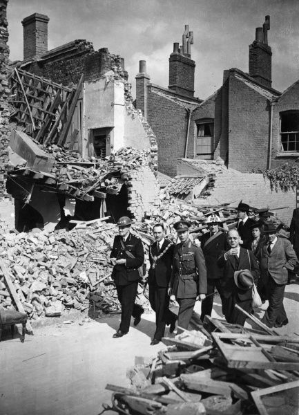 King George VI inspecting destroyed homes, part of the damage done by German air raids over London during the Blitz